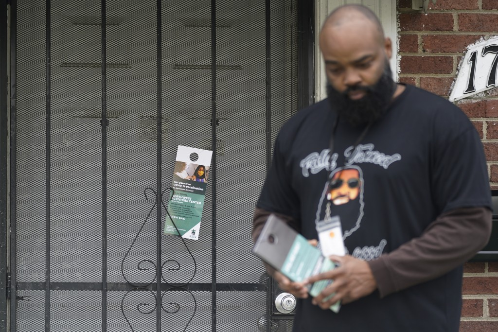 Anthony Brinson leaves a flyer on a home in Detroit, Tuesday, May 4, 2021. Officials are walking door-to-door to encourage residents of the majority B...