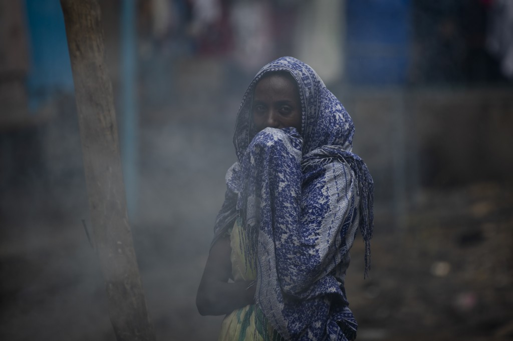 """A displaced Tigrayan woman covers her face from the smoke of a wood fire as she prepares """"Injera"""" flatbread at the Hadnet General Secondary School whi..."""