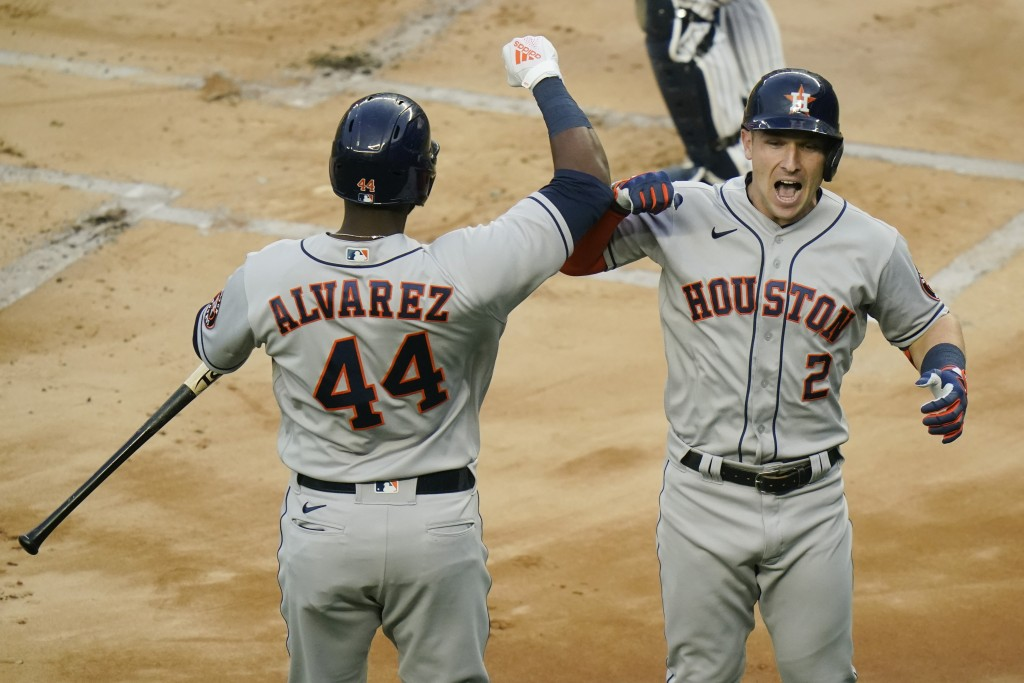 Houston Astros' Alex Bregman, right, celebrates with Yordan Alvarez, left,  after hitting a home run during the first inning of a baseball game agains...