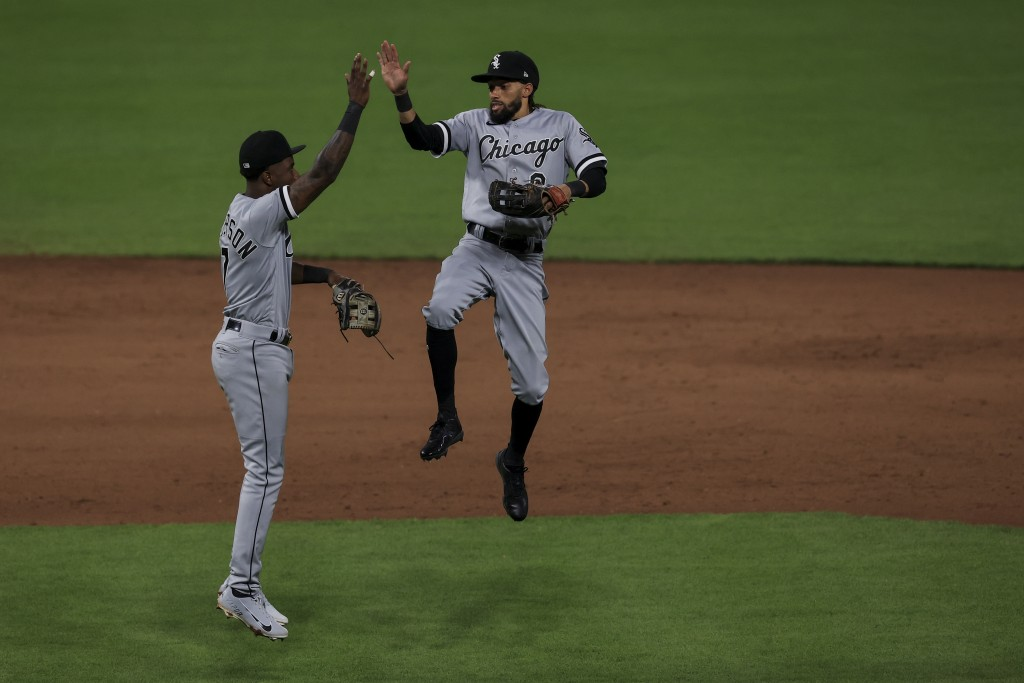 Chicago White Sox Tim Anderson, left, celebrates with Billy Hamilton after the final out of the ninth inning of a baseball game against the Cincinnati...