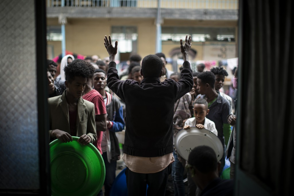 An organizer raises his hands to ask displaced Tigrayans to queue in an orderly way as they wait to receive food at the Hadnet General Secondary Schoo...