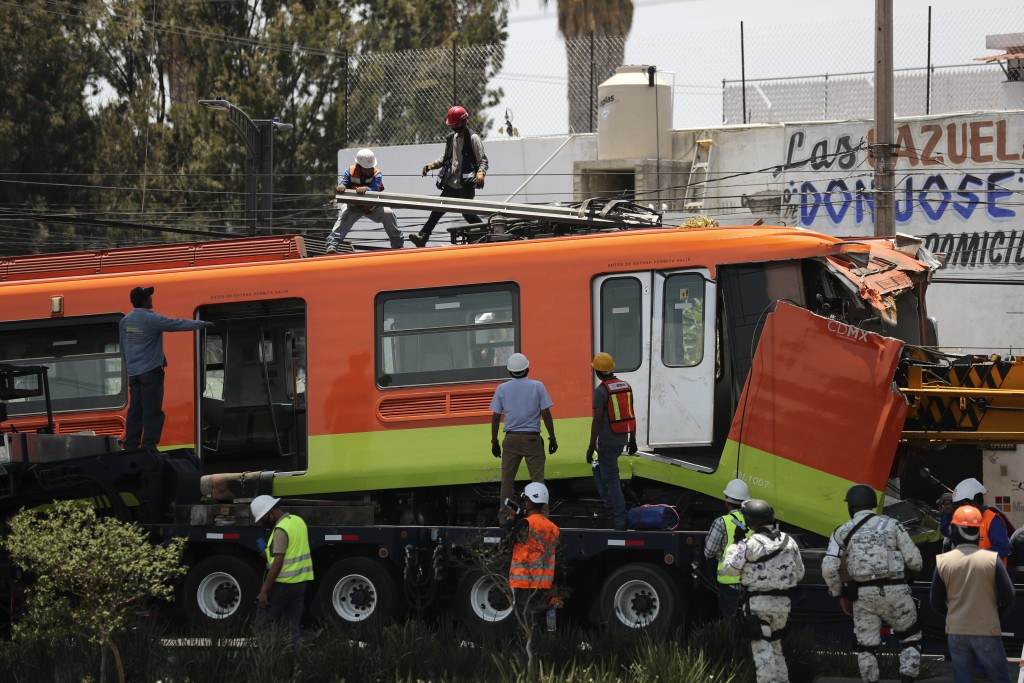 Workers remove a damaged subway car after it was lowered, with the help of a crane, to the ground from a collapsed elevated section of the metro, in M...