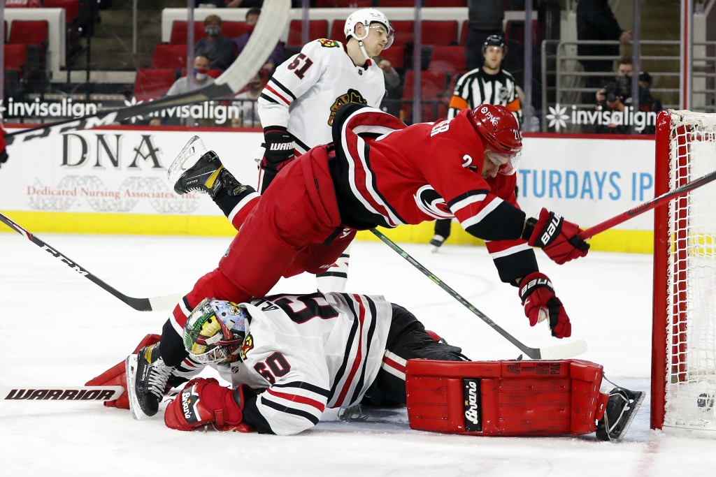 Carolina Hurricanes' Nino Niederreiter (21) collides with Chicago Blackhawks goaltender Collin Delia (60) after scoring a goal during the second perio...