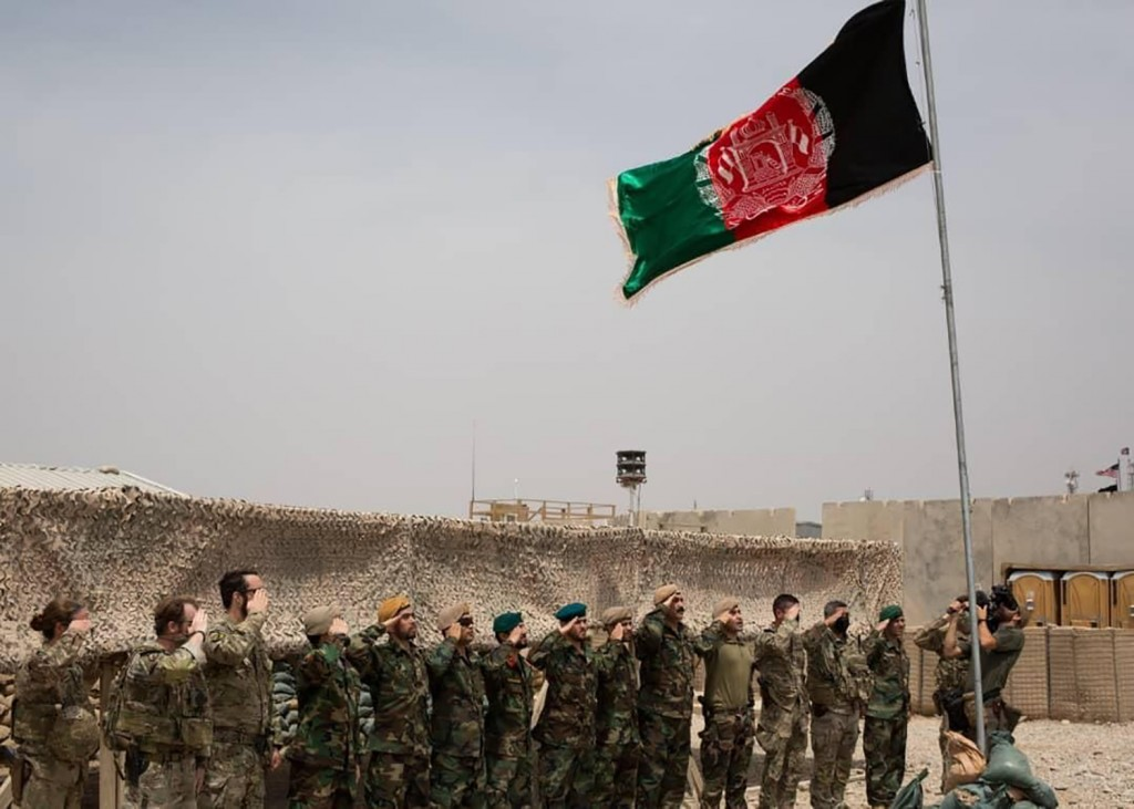 An Afghan flag flies as American and Afghan soldiers salute during a handover ceremony from the U.S. Army to the Afghan National Army, at Camp Anthoni...