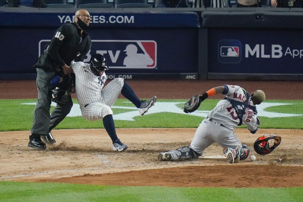 New York Yankees' Rougned Odor falls into the home plate umpire after running past Houston Astros catcher Martin Maldonado, right, to score during the...