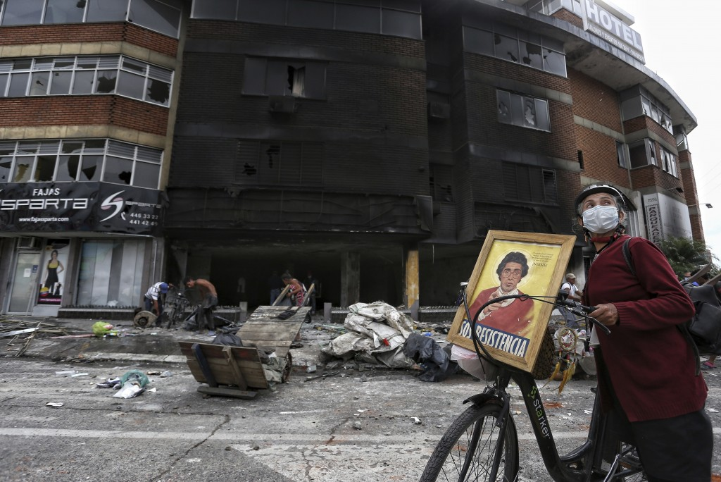A woman walks past La Luna hotel that was burned and looted Monday night during a protest against tax reform in Cali, Colombia, Tuesday, May 4, 2021. ...