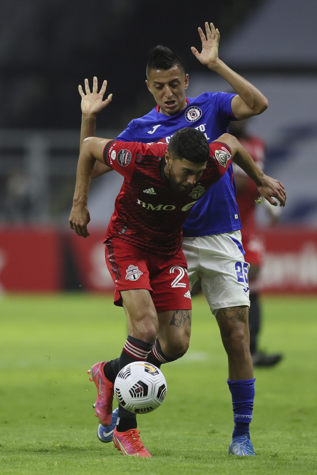 Jonathan Osorio of Canada's Toronto FC, front, and Roberto Alvarado of Mexico's Cruz Azul compete for the ball during CONCACAF Champions League quarte...