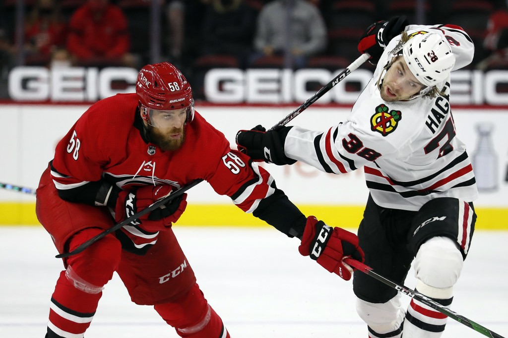 Chicago Blackhawks' Brandon Hagel (38) tangles with Carolina Hurricanes' Jani Hakanpaa (58) during the second period of an NHL hockey game in Raleigh,...