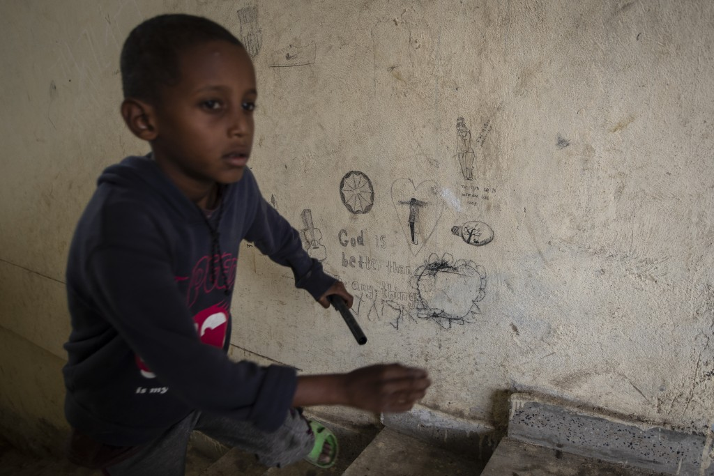 """A displaced Tigrayan boy runs up stairs past graffiti reading """"God is better than any thing"""" at the Hadnet General Secondary School which has become a..."""