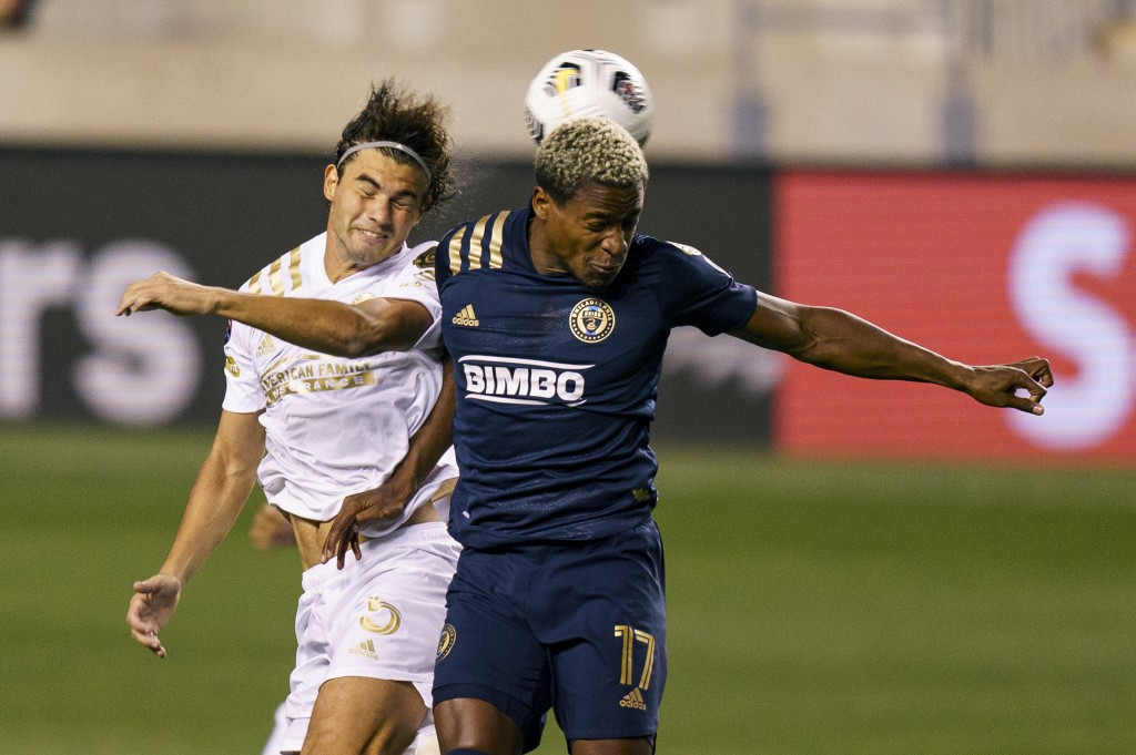 Atlanta United's Santiago Sosa, left, heads the ball away from Philadelphia Union's Sergio Santos, right, during the first half of a CONCACAF Champion...