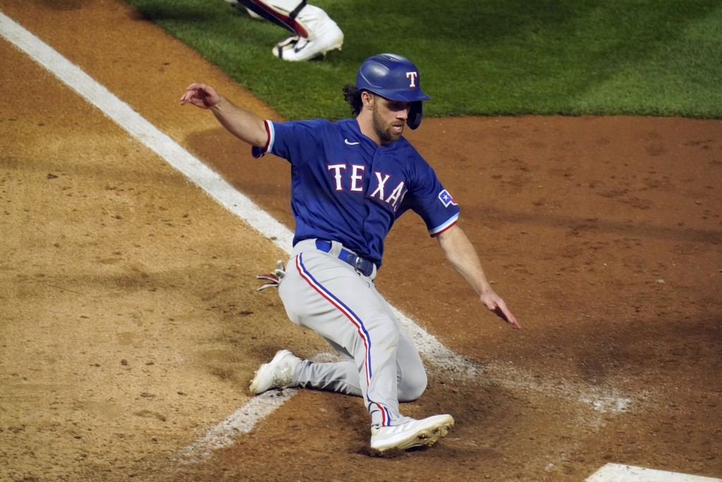 Texas Rangers' Charlie Culberson slides home to tie the score on a sacrifice fly ball by Isiah Kiner-Falefa in the ninth inning of a baseball game, Tu...