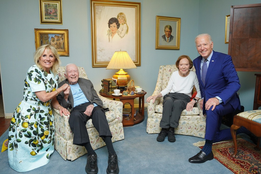 In this April 30, 2021, photo released by The White House, former President Jimmy Carter and former first lady Rosalynn Carter pose for a photo with P...