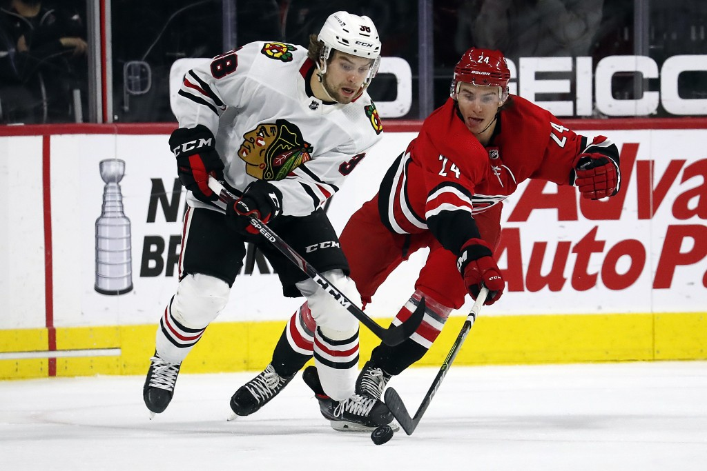 Carolina Hurricanes' Jake Bean (24) battles for the puck with Chicago Blackhawks' Brandon Hagel (38) during the second period of an NHL hockey game in...