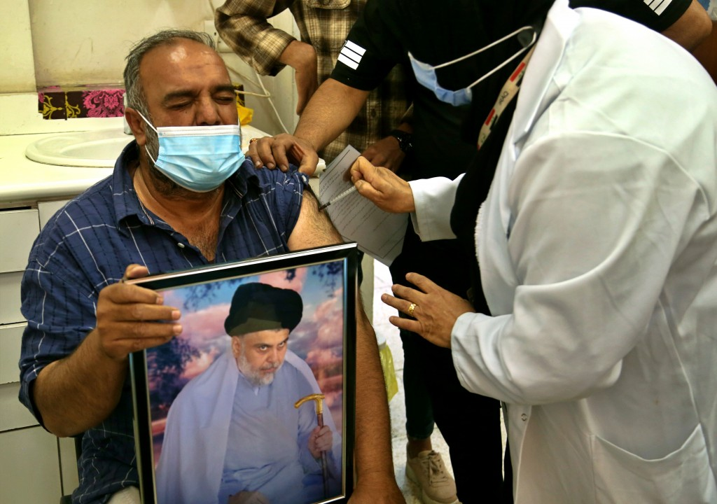 A follower of populist Shiite cleric Muqtada al-Sadr holds a picture of him while receiving a dose of the Chinese Sinopharm coronavirus vaccine at a c...