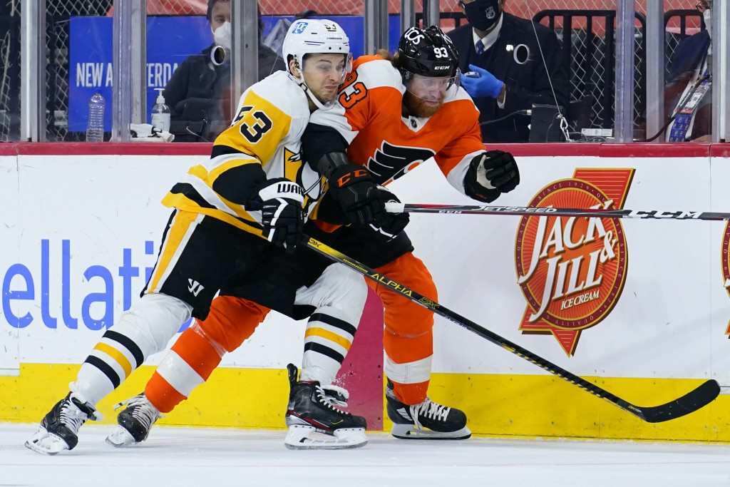 Pittsburgh Penguins' Teddy Blueger, left and Philadelphia Flyers' Jakub Voracek battle for the puck during the third period of an NHL hockey game, Tue...