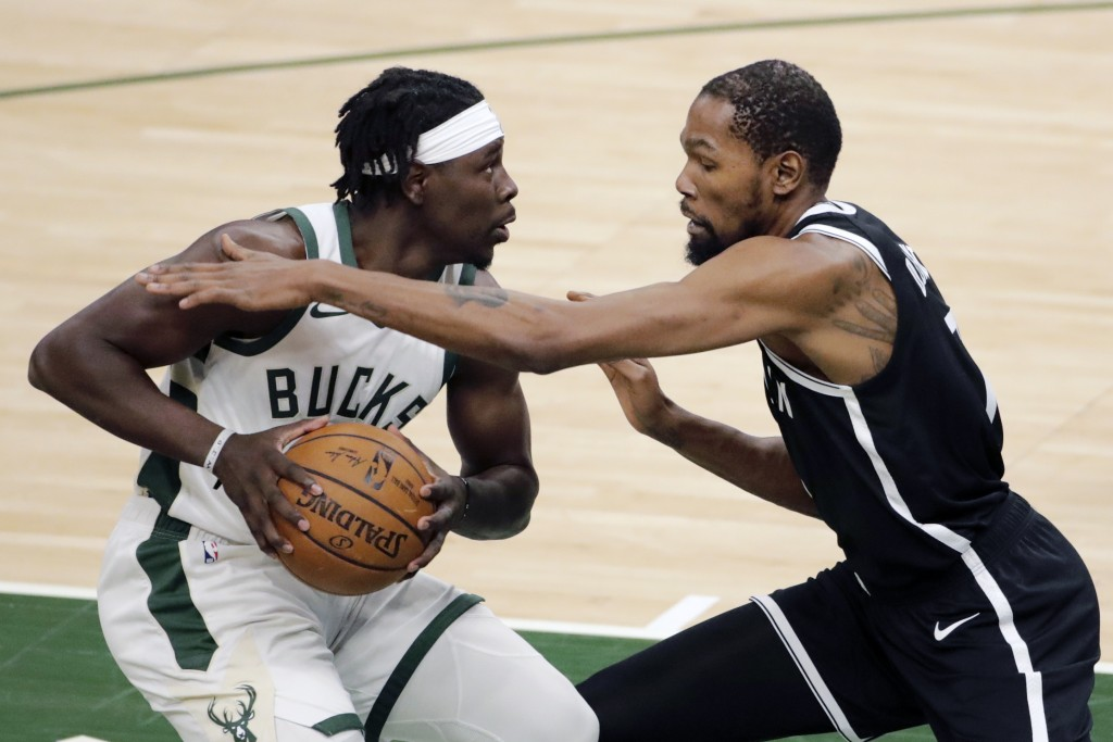 Milwaukee Bucks' Jrue Holiday, left, drives to the basket against Brooklyn Nets' Kevin Durant during the first half of an NBA basketball game Tuesday,...