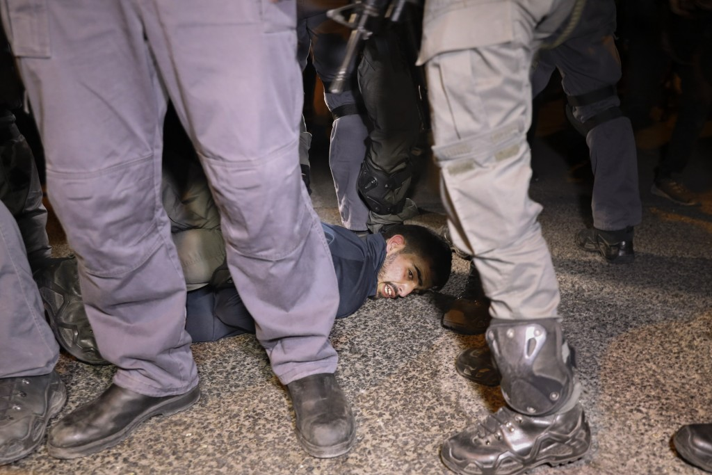 Israeli police officers detain a Palestinian demonstrator during a protest against the planned evictions of Palestinian families in the Sheikh Jarrah ...