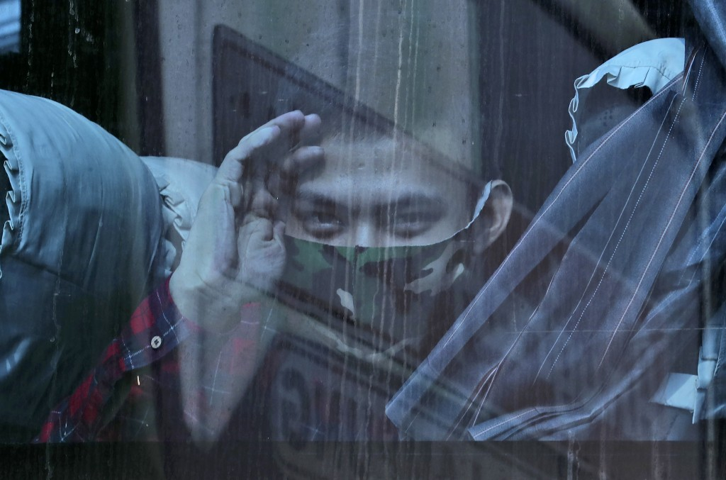 A man looks out from inside a bus at the Kalideres bus terminal in Jakarta, Indonesia, Wednesday, May 5, 2021. The mass exodus out of major cities in ...