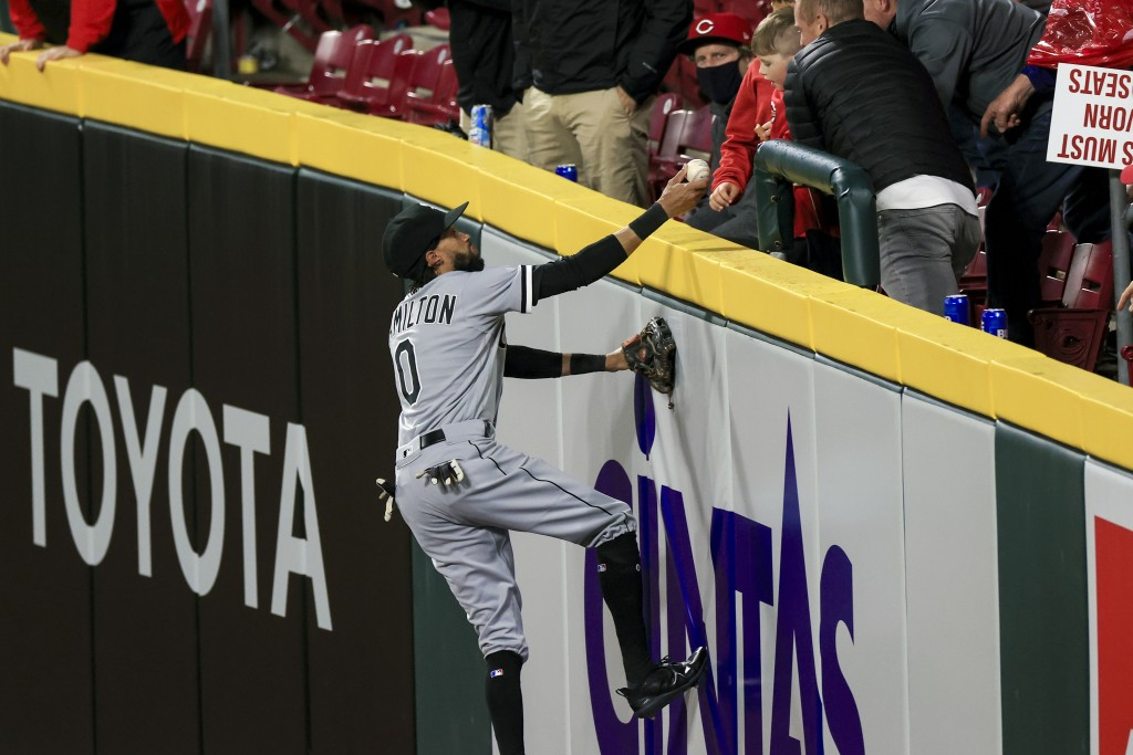 Chicago White Sox Billy Hamilton climbs the outfield wall to give the ball to a fan prior to the bottom of the sixth inning of a baseball game against...
