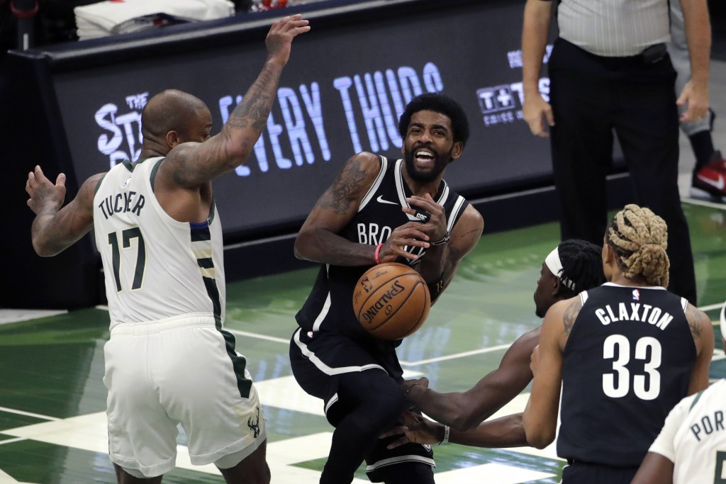Brooklyn Nets' Kyrie Irving controls the ball as he drives between Milwaukee Bucks' P.J. Tucker (17) and Jrue Holiday during the first half of an NBA ...