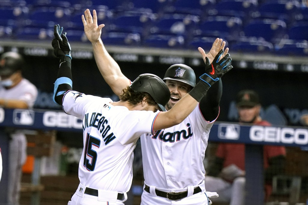 Miami Marlins' Brian Anderson (15) celebrates with Adam Duvall after hitting a three-run home run during the first inning of a baseball game against t...