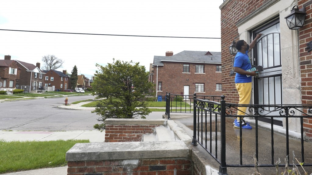 Robert Day knocks on a door before leaving a flyer on a home in Detroit, Tuesday, May 4, 2021. Officials are walking door-to-door to encourage residen...