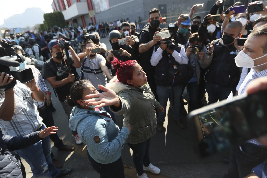 A woman demands information from a lawmaker of people injured when a metro overpass collapsed, near the site of the wreckage in Mexico City, Tuesday, ...