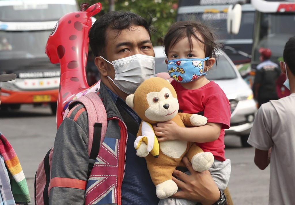 A man carries his daughter at the Kalideres bus terminal in Jakarta, Indonesia, Wednesday, May 5, 2021. The mass exodus out of major cities in the wor...