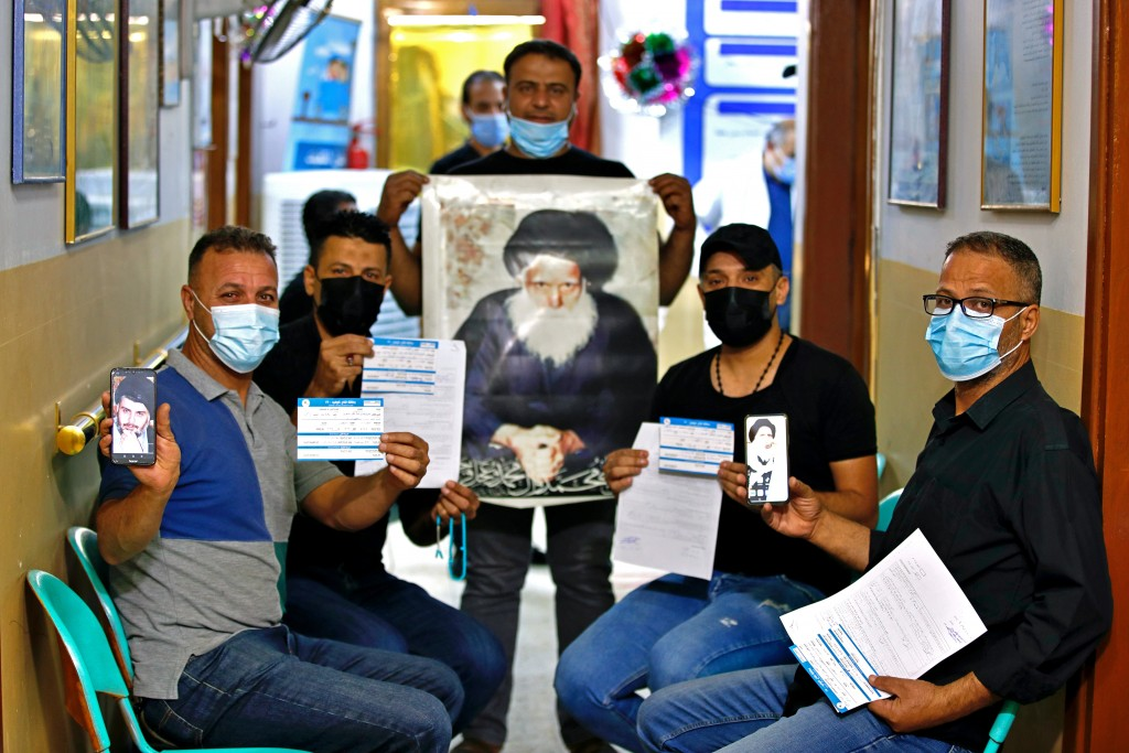Followers of Shiite cleric Muqtada al-Sadr, pose for a photo holding pictures of him and his father and their vaccination cards as they wait to receiv...
