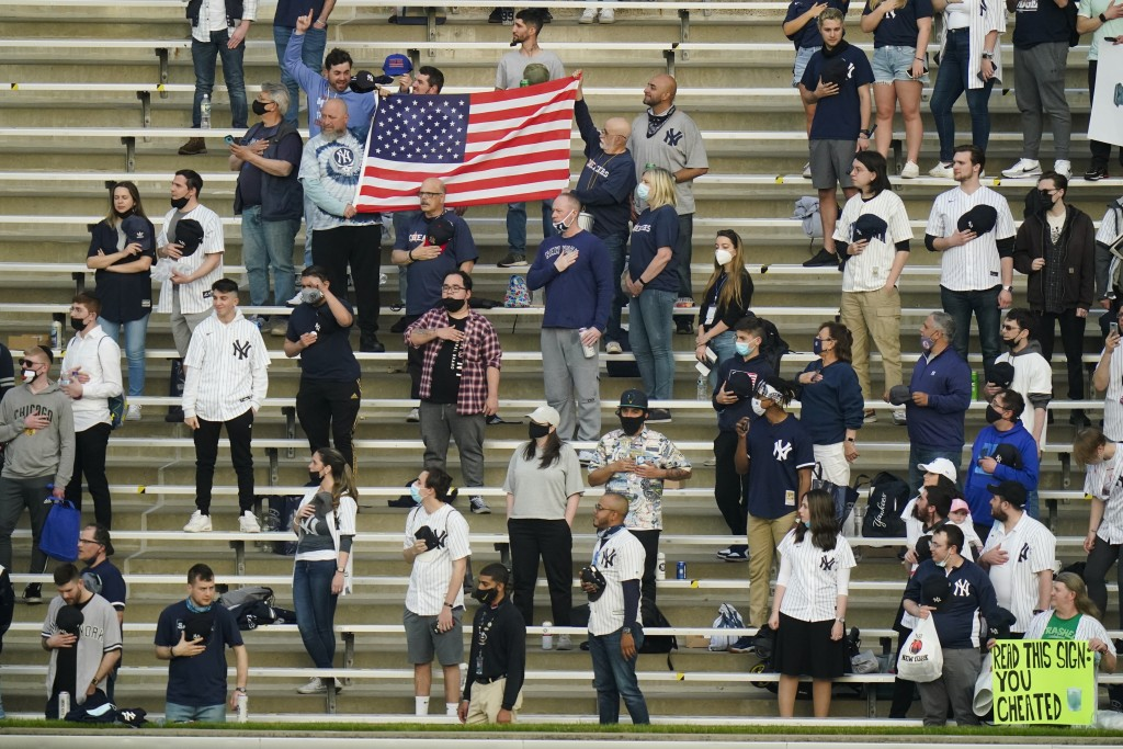 Fans stand during the playing of the national anthem before a baseball game between the New York Yankees and the Houston Astros Tuesday, May 4, 2021, ...