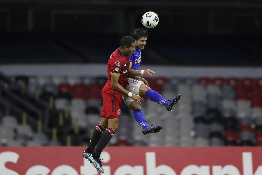 Justin Morrow of Canada's Toronto FC, left, and Adrian Aldrete of Mexico's Cruz Azul fight for the ball during a CONCACAF Champions League quarterfina...