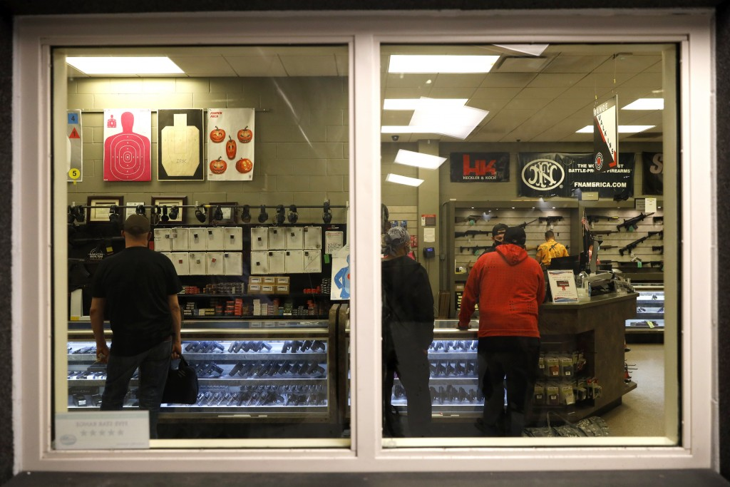 Customers stand inside the gun shop area of Maxon Shooter's Supplies and Indoor Range, as seen from the shooting range, Friday, April 30, 2021, in Des...