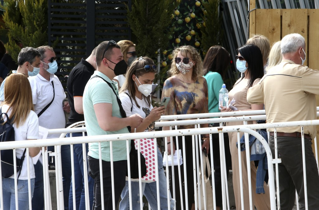 People wait in line to enter the COVID-19 vaccination center, at A1 Arena in Skopje, North Macedonia, on Tuesday, May 4, 2021. The European Union star...