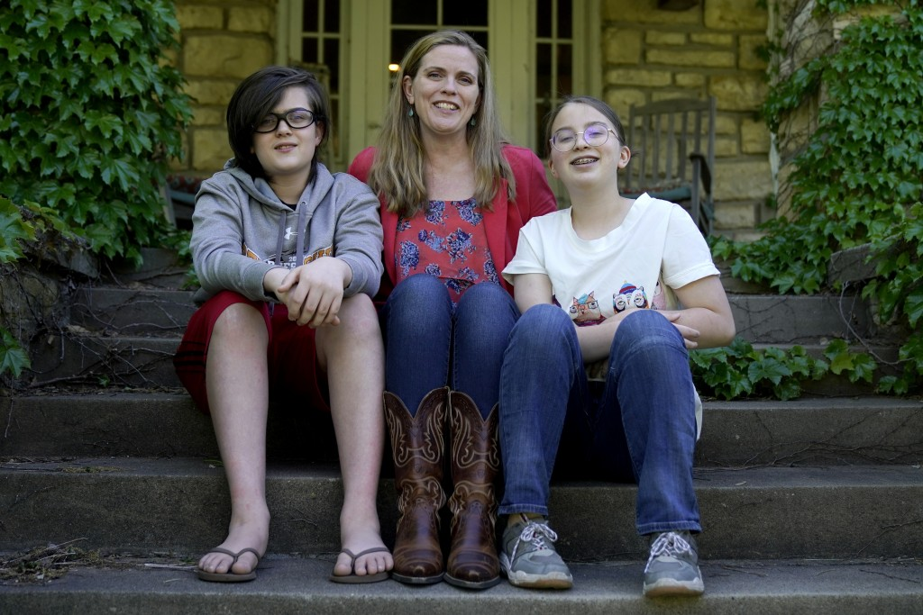 Heather Ousley sits with her older children Elliannah, 15, right, and Samuel, 13, in front of their home in Merriam, Kan, Tuesday, May 4, 2021. Ousley...