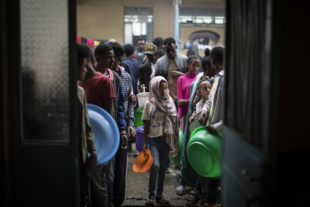 Displaced Tigrayans queue to receive food at the Hadnet General Secondary School which has become a makeshift home to thousands displaced by the confl...