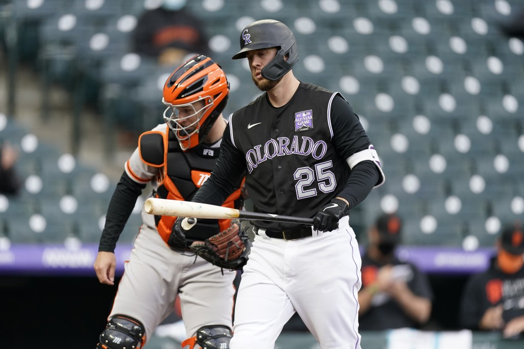 Colorado Rockies' C.J. Cron, front, reacts after striking out as San Francisco Giants catcher Buster Posey looks on in the seventh inning of game one ...