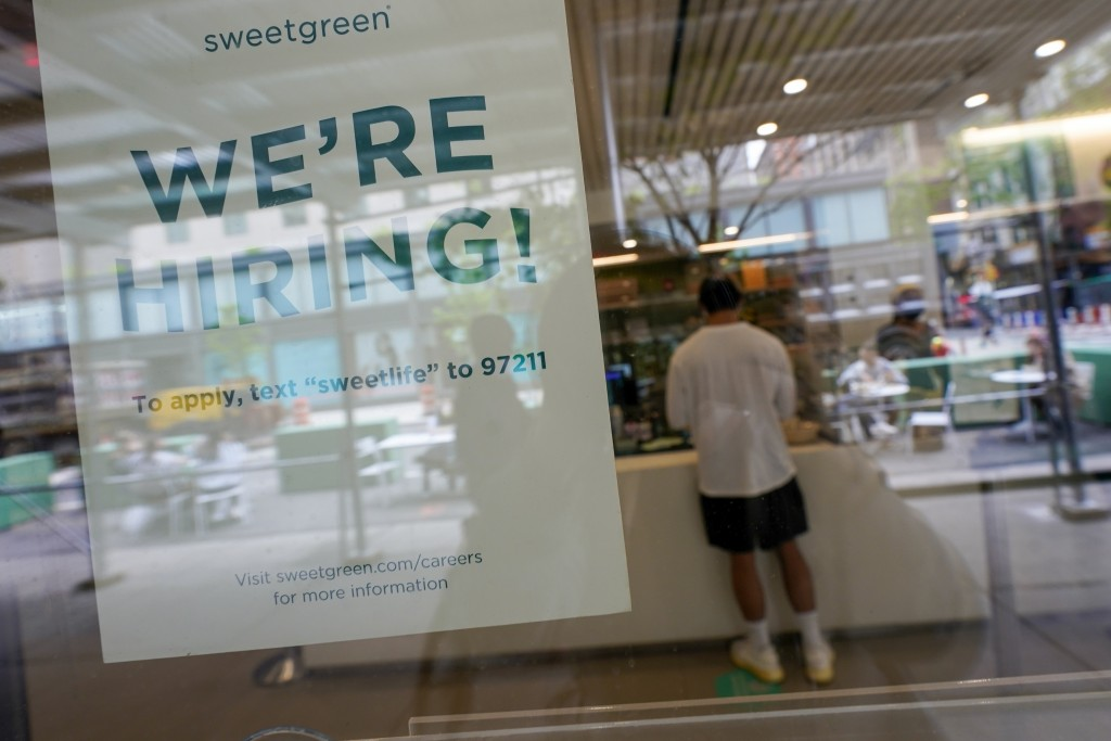 A signs announcing they are hiring hangs in the window of a restaurant in the Greenwich Village neighborhood of Manhattan in New York, Tuesday, May 4,...