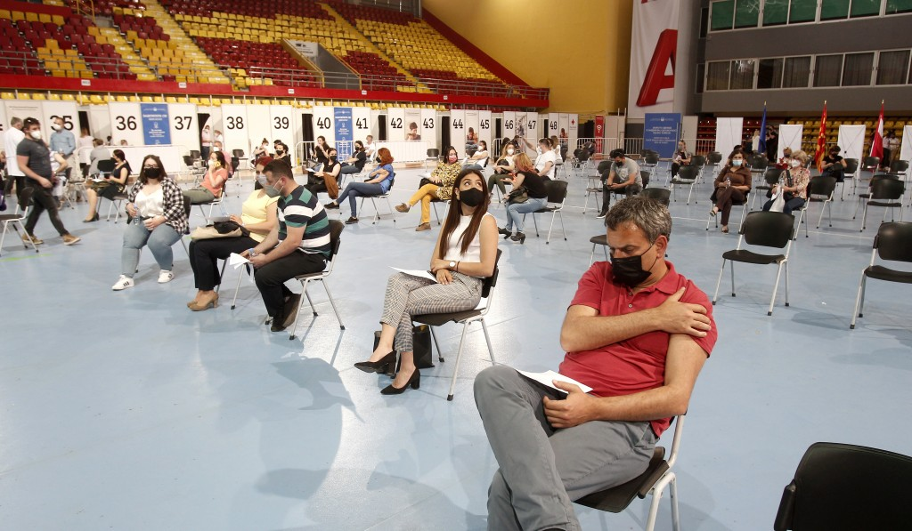 People wait after being vaccinated at the center for mass vaccination against COVID-19, at A1 Arena in Skopje, North Macedonia, on Tuesday, May 4, 202...