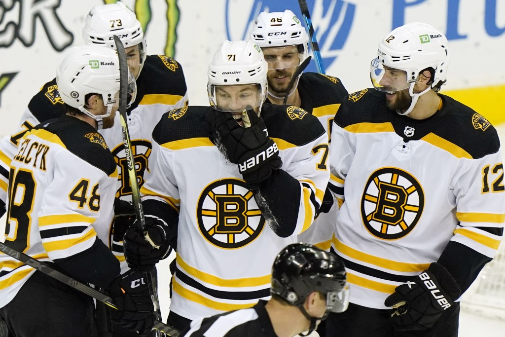 Boston Bruins left wing Taylor Hall (71) laughs with teammates after inadvertently scoring a goal against the New Jersey Devils during the second peri...