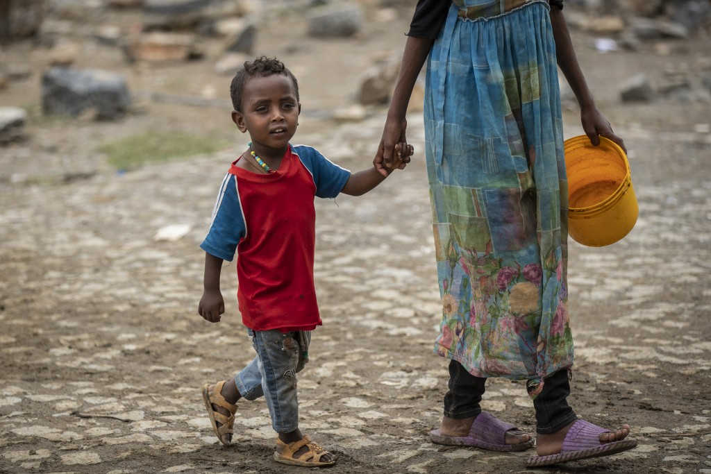A displaced Tigrayan boy walks with a relative to receive food at the Hadnet General Secondary School which has become a makeshift home to thousands d...