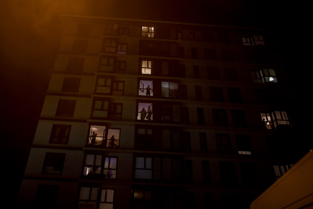 People watch from their houses as the supporters of far-right Vox party react outside the Vox party headquarters in Madrid, Spain, Tuesday, May 4, 202...