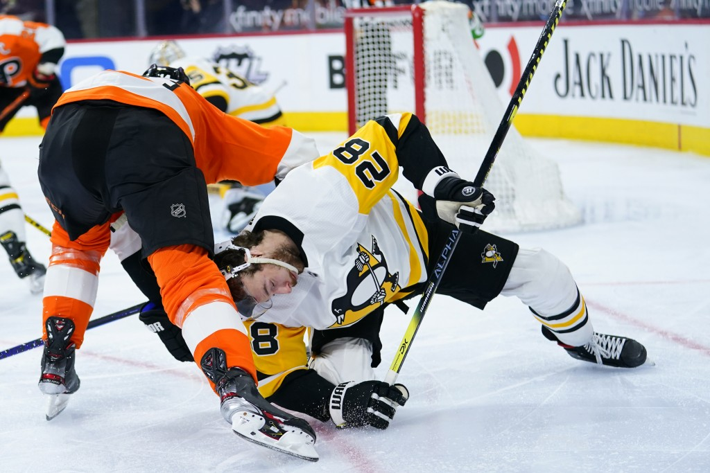 Pittsburgh Penguins' Marcus Pettersson, right, collides with Philadelphia Flyers' Sean Couturier during the third period of an NHL hockey game, Tuesda...