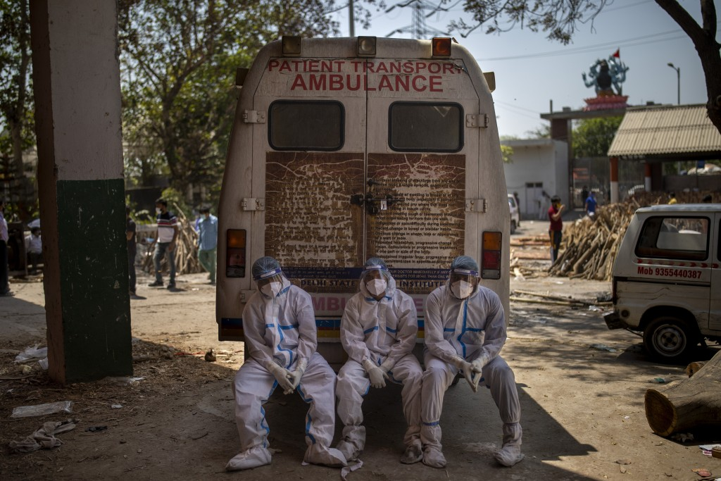 FILE - In this April 24, 2021, file photo, exhausted workers who carried the dead for cremation sit on the rear step of an ambulance in New Delhi, Ind...