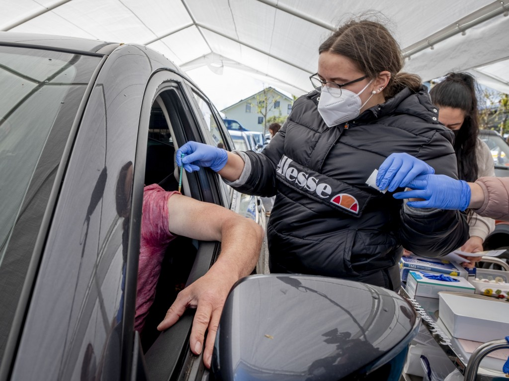 A man sits in his car as he is vaccinated with AstraZeneca in a tent on the parking lot of a supermarket in Pforzheim, southern Germany, Wednesday, Ma...