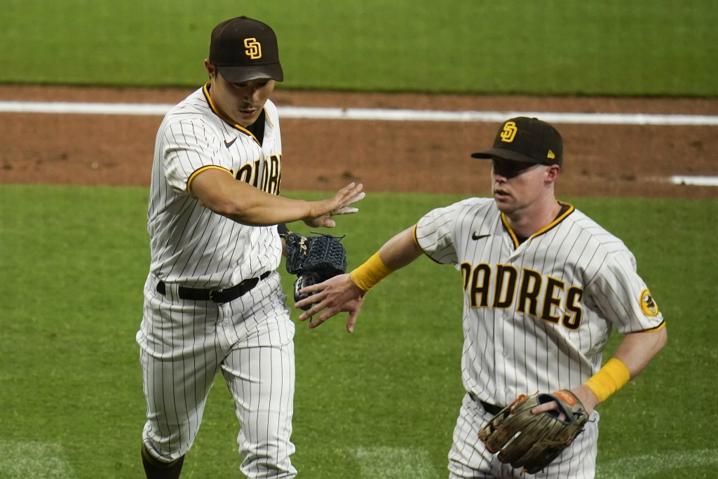 San Diego Padres shortstop Ha-Seong Kim, left, is greeted by teammate second baseman Jake Cronenworth during the second inning of a baseball game agai...
