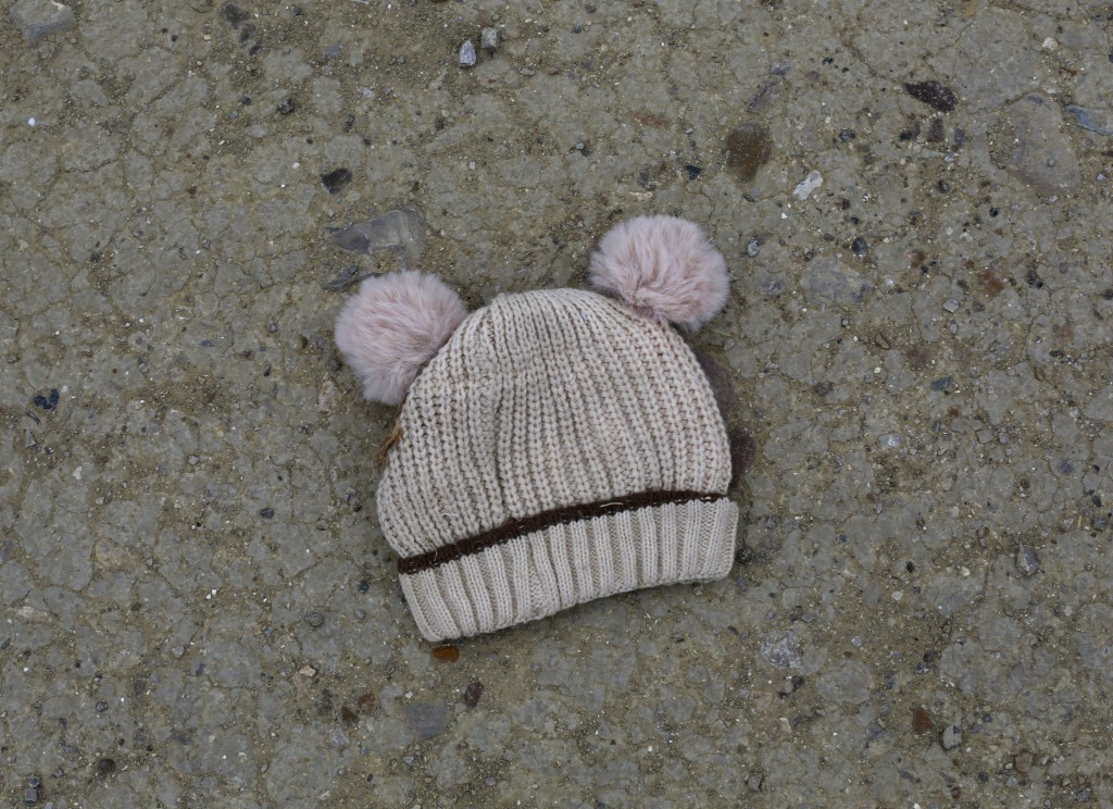 FILE - In this March 28, 2021, file photo, a child's knitted cap lies on the ground near the banks of the Rio Grande river in Roma, Texas. Confronted ...