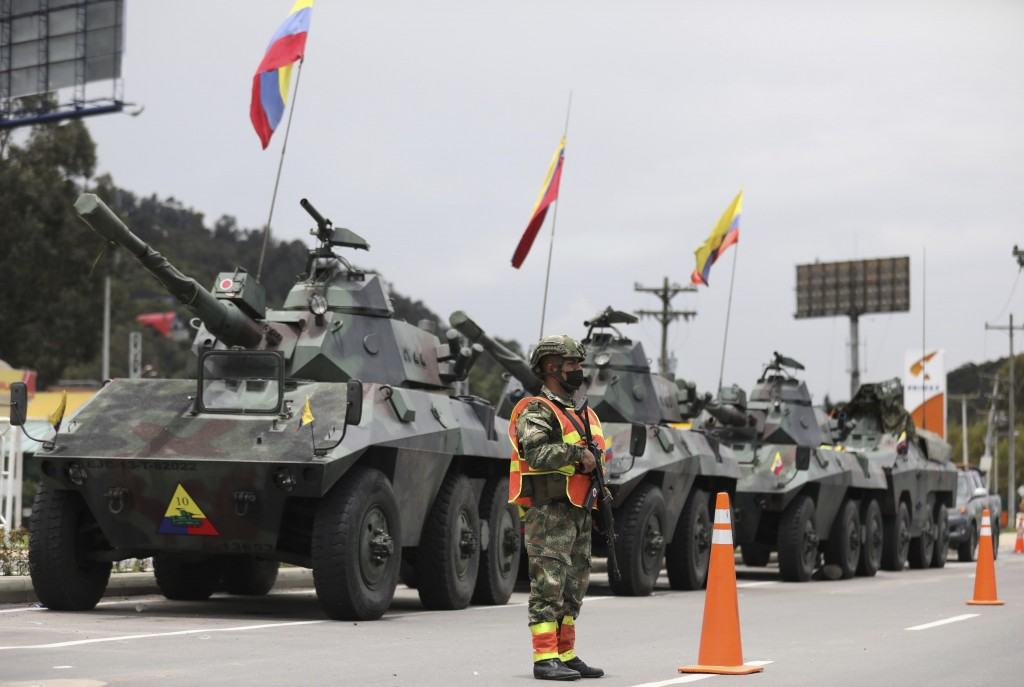 Soldiers and army tanks guard toll booths to keep protesters from damaging them, on the outskirts of Bogota, Colombia, Tuesday, May 4, 2021. Colombia'...