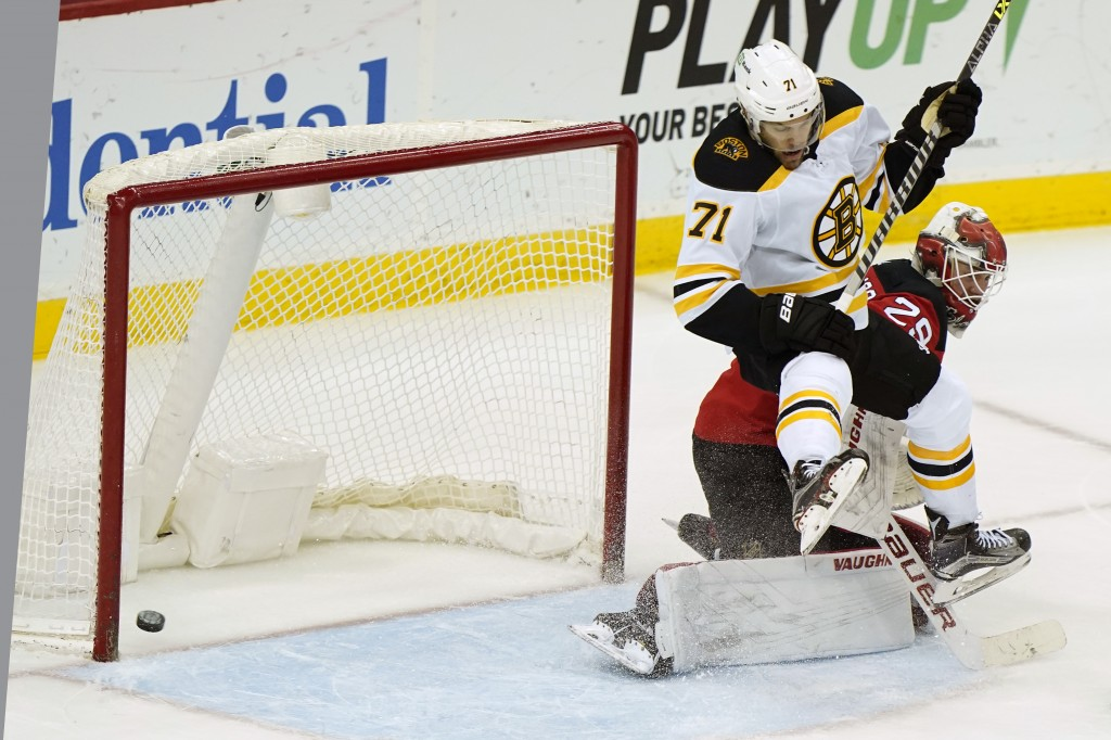The puck goes in on a shot by Boston Bruins left wing Taylor Hall (71) who leaps above New Jersey Devils goaltender Mackenzie Blackwood (29) during th...