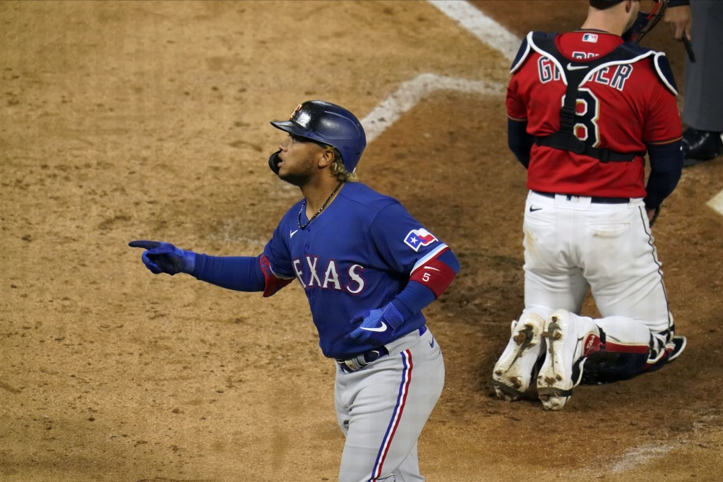 Texas Rangers' Willie Calhoun scores on a solo home run in the ninth inning of a baseball game, Tuesday, May 4, 2021, in Minneapolis. (AP Photo/Jim Mo...