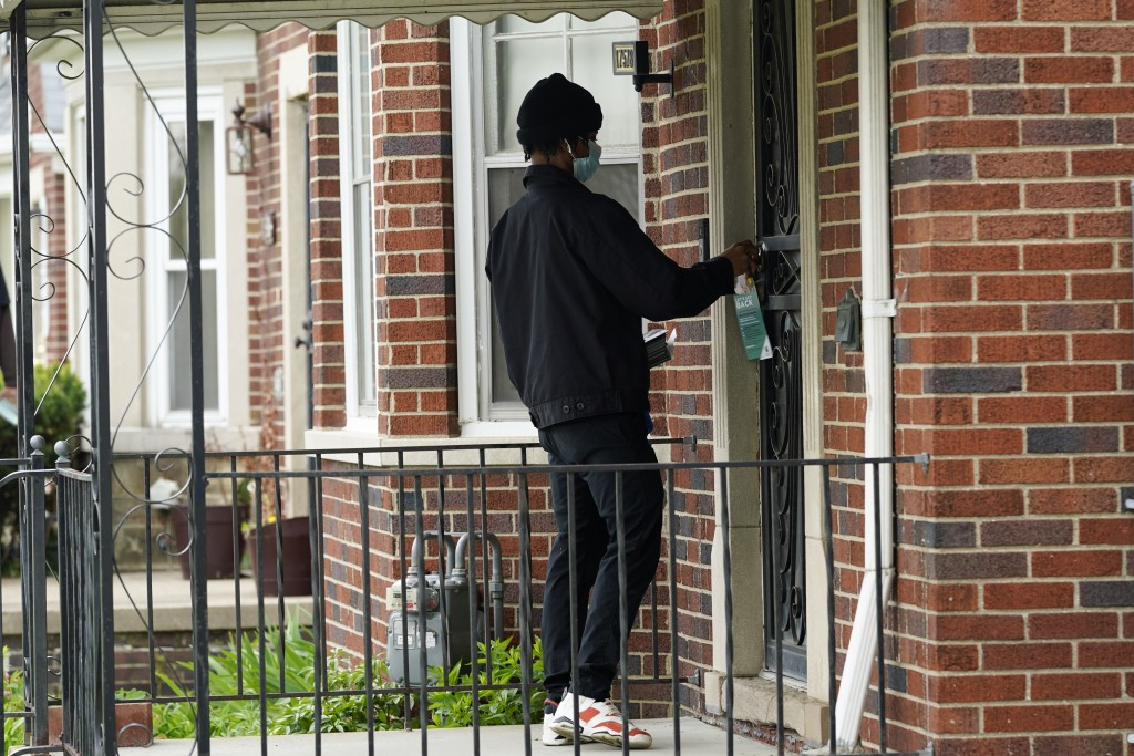 Deares Carey leaves a flyer on a home in Detroit, Tuesday, May 4, 2021. Officials are walking door-to-door to encourage residents of the majority Blac...
